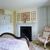 A bed room in a rustic country house with an open fireplace and a built-in cupboard