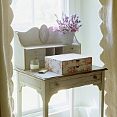 A white, wooden davenport with gold inlays and drawers in a window niche
