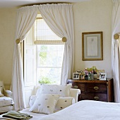An elegant, country-house style bedroom with a white curtains and a blind at the window