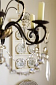 Detail of a candle holder with glass decorations and a dresser with plates