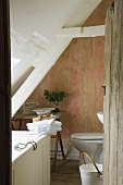 An open wooden door with a view into a partially renovated attic bathroom in an old country house