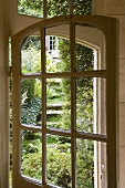 An old glass terrace door with a view into a garden