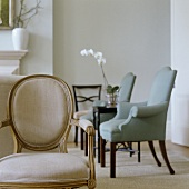 An antique upholstered chair with a light back and a view of upholstered armchairs