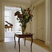 A large bunch of flowers on a Rococo-style occasional table with a view into a room with a piano