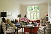 A living room with comfortable upholstered furniture and a sofa with occasional tables in front of a window with a view
