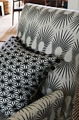 A grey chair with an abstract pattern and a grey cushion with a black star pattern