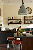 An open-plan kitchen in a country house - a metal lamp over a kitchen counter with red upholstered bar stools and wooden shelves on the wall