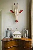 A painted wooden antelope head hanging above a Biedermeier-style davenport