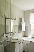 A wash basin and a mirror with wall lighting on a white wooden wall in a country-house style bathroom