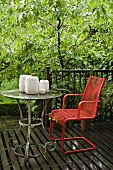 A red garden chair and a set of candles on a vintage metal table on a wooden terrace