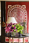 Flowers on a wooden table in front of a red ethnic cloth with a perforated pattern
