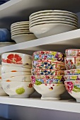 Brightly painted bowls and plates on a white shelf