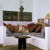 A Mediterranean-style living room corner - and occasional table with a metal tray and a candlestick in front of a concrete, upholstered pedestal with cushions