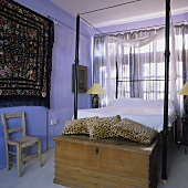 A Mediterranean bedroom - a wooden chest with leopard-print cushions in front of a metal four-poster bed