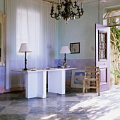 Table lamps with white shades on a desk with angled legs in a Mediterranean-style blue-coloured living room with a chess-board floor