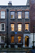 An English town house at dusk with a brick facade and blue transom windows