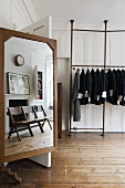White wooden panelling in a living room - a studio with a tailor's mirror with a reflection and jackets hanging on a clothes rack