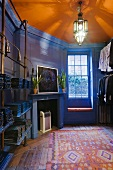 Bright colours in a tailor's studio - shadows playing on an orange ceiling and shelves with pattern books in front of a blue wood panelled wall