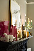 Pink vases and burning candles on a black mantelpiece