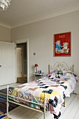 A patchwork quilt on an antique, white metal bed standing on white-painted floor-boards in a child's bedroom