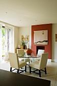 Eleganter Wohnraum mit gepolsterten weissen Stühlen und rundem Glastisch vor Kamin in rotgetönter Wandscheibe