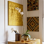 Geometric patterns on canvases in the corner of a living room and white orchids in a pot