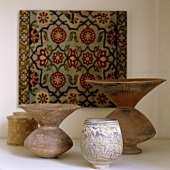 Antique folk art style stone containers in front of a picture with an oriental design