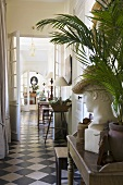 A bust and a palm tree on a wooden wall table in the corridor of a country house with a black and white tiled floor