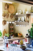 A view onto a light grey plate rack and hanging baskets in the kitchen of a country house