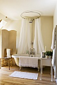 A bathroom in a country house with an antique bathtub with feet and a white shower curtain