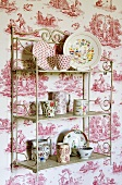 Crockery on an antique metal shelf on a wall papered with country images