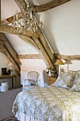 A queen-sized bed and a chandelier in a rustic attic room in a country house