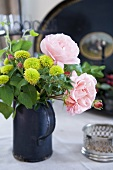 A bunch of flowers featuring pink roses in an old metal jug