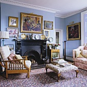 A blue-painted fireplace room with an upholstered occasional table and armchairs on an oriental rug
