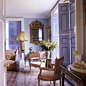 Barockstühle mit Beistelltisch vor raumhohen Fensterläden und Spiegel mit Goldrahmen im fliederfarbenen Wohnraum