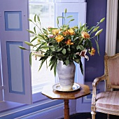 A bunch of flowers featuring yellow roses on a delicate wooden occasional table in front of lilac-painted window shutters
