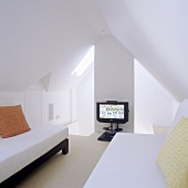 Attic room (minimalist design) with single beds under a pitched roof and a TV