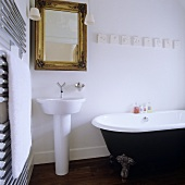 A designer wash basin and a mirror with a gold frame and an antique bathtub with feet in a bathroom