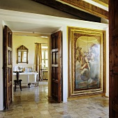 An elegant anteroom in a country house with a painted, built-in cupboard and a view through an open wooden door into a bathroom