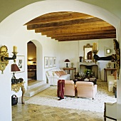 A view through a arched doorway into an open living room in a finca with a rustic wood beam ceiling and a white sofa in front of a fireplace