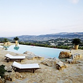 Loungers on a natural stone floor by a pool with a view of the Spanish landscape