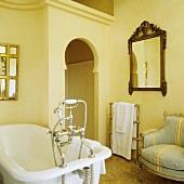A bathtub with antique taps in front of a false front with an Oriental-style door opening