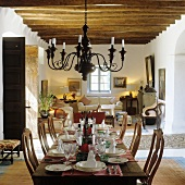 A chandelier hanging from a wooden beamed ceiling above a festively laid dining table in an open plan living-room-cum-dining-room