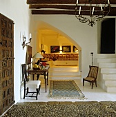 An elegant foyer in a finca with white concrete stairs and a view onto a comfortable padded seating corner