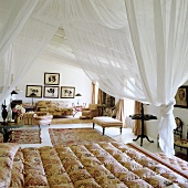 A white canopy above a bed and elegant chairs and rugs in a bedroom
