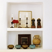 A concrete whitewashed wall niche with candle holders, busts and jars