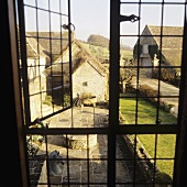 A view through a window onto a courtyard with flagstones and a lawn in front of an English country house