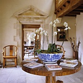 Orchids in a blue and white porcelain bowl on an occasional table and a view onto an antique Greek attica above a door into another room