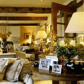 A living room in a country house with a rustic wood beam ceiling and an occasional table with photos and Oriental brass figures