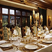 A festively laid table set with silver candle sticks in front of a window in the dining room of a country house